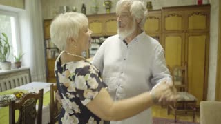 Lovely senior man and senior woman dancing together at home