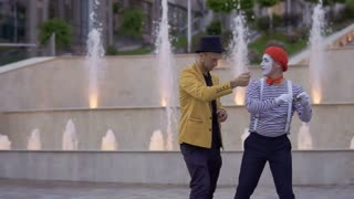 Magician showing magic trick to a mime with playing card