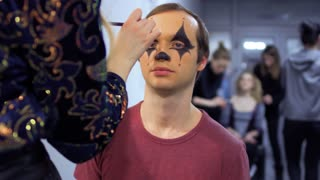 Make-up artist makes greasepaint to a young man in theatre