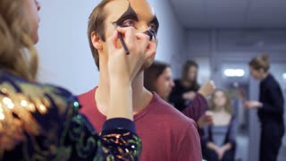 Makeup artist is making greasepaint to the actor in theatre