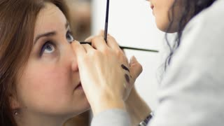 Makeup artist prepares young girl for performance in theatre