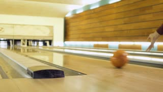 male hand throws bowling ball and hits bowling pins