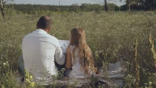 Man and little girl read book at meadow
