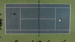 Man and woman play tennis at the court