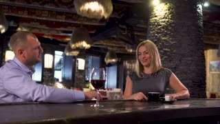 Man and woman sitting near bar counter and drinking wine and coffee