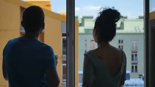 Man and woman talks near the window