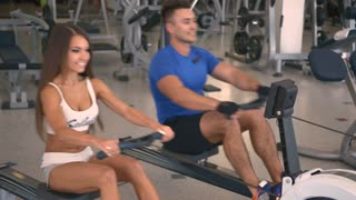 Man and woman training on a rowing machine in gym