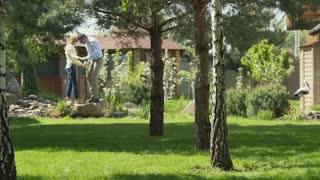 Man carries the woman through the garden