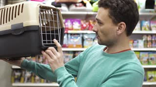 Man choose box for transportation his cat in the pet shop