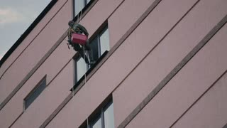 Man climber prepares for cleaning windows