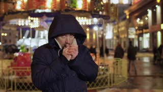 Man feels cold and blows warm air on his hands, tries to warm up
