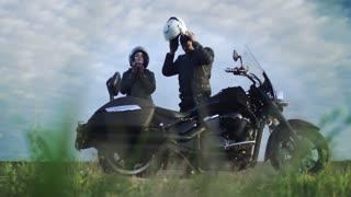 Man help his girl with helmet of motorcycle, couple preparing to ride