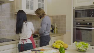 Man help his wife to cook dinner