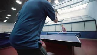 Man in blue T-shirt playing a ping-pong with woman at the court