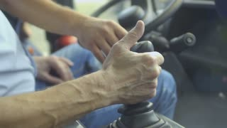 Man inspects gearbox in tractor
