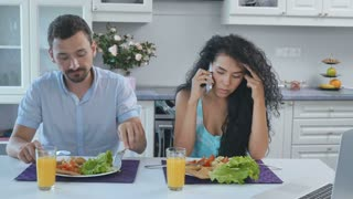 Man is annoyed during the breakfast because of wife talks on phone