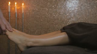 Man massaging the girl's fingers on the left foot in the spa