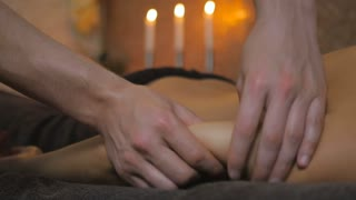 Man massaging the girl's hand in the spa