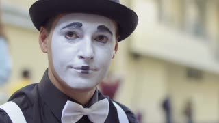 Man mime put on his hands white gloves