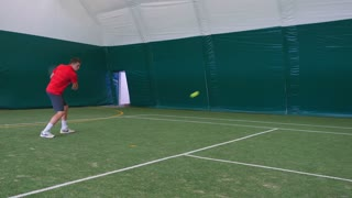 Man playing tennis with young guy on grass court