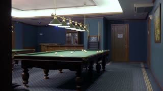 Man rubs billiard cue with a chalk