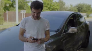 Man smiling and texting with friends by phone leaning on his car