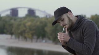 Man smokes cigarette at the bridge