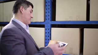 Man stands in the warehouse and keeps the tablet