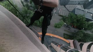 Man steeplejack climbs down the building