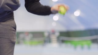 Man throws and successfully catches a tennis ball