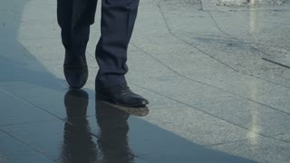 Man walks near the fountain, wet shoes, close-up