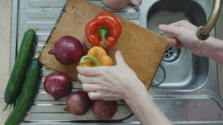 Man washes red and yellow peppers