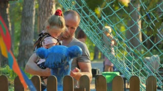 Man with little daughter observes a monument in the park