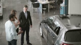 Manager demonstrates the car to young couple in car dealership