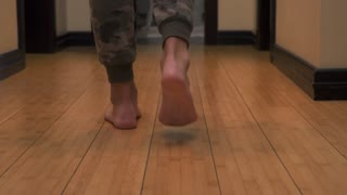 Man's legs walk from one room to another
