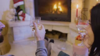 Married couple drinks wine and relaxing near fireplace