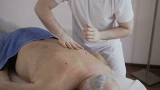 Masseur massage old man's back in slowmotion