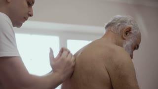 Masseur massages a back of old man