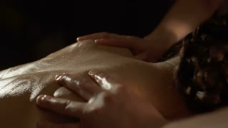 Masseur massages back of young woman with olive oil