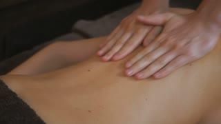 Masseur massages girl's naked back in salon