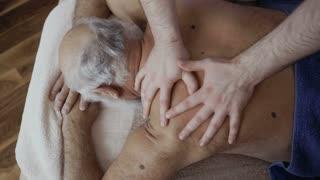 Masseur massages shoulder of old man