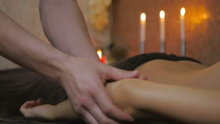 Masseur massaging the girl's hand in the spa