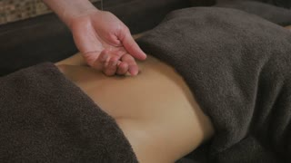 Masseur pours oil in the hand and start massaging the girl's stomach
