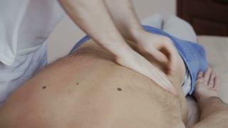 Masseur professionally massages back of senior man