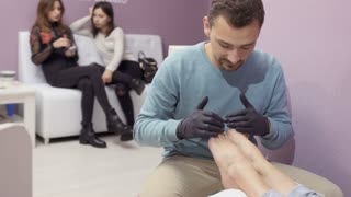 Master makes pedicure to young woman