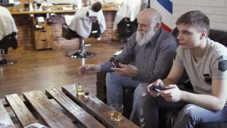 Mature man and young guy drinks alcohol during playing video game