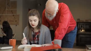 Mature man helps young student to make homework