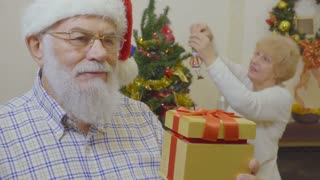 Mature man make suprise for his wife at Christmas