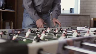 Mature man plays table soccer