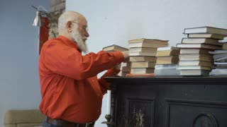 Mature man searches information in old book